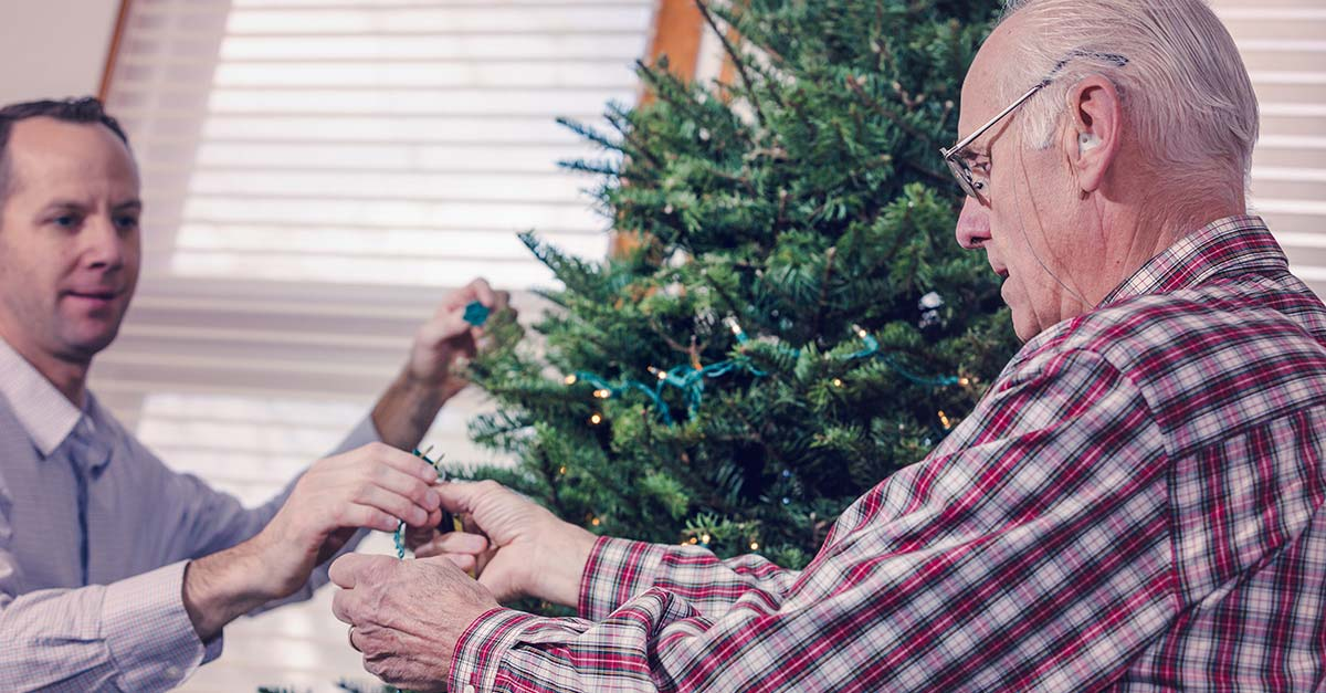 Elderly man putting up tree with family